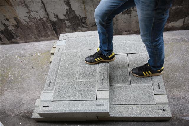 運用廢棄塑料製成人行步道磚,將塑料做有益環境的運用。(台灣積層提供)