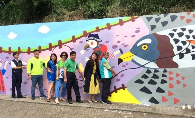 在超萌巨大版「灰面鵟鷹」路邊坡彩繪牆面前,與會來賓攜手轉化風箏視覺意象,手拉著風箏線表現情境互動趣味。(台中市政府提供)