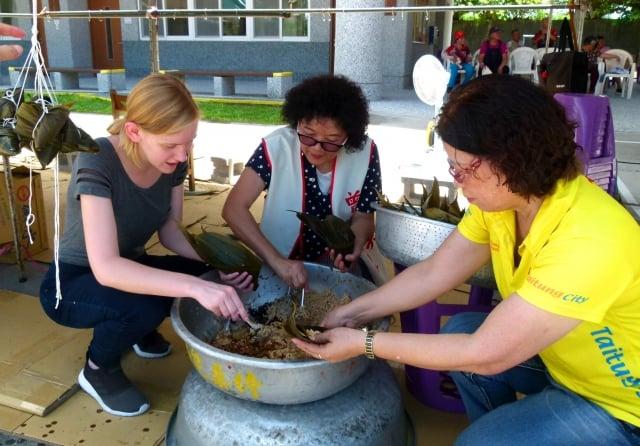 光明國小外籍英語教師柯凱玲(左)體驗端午包粽的樂趣。(記者龍芳/攝影)