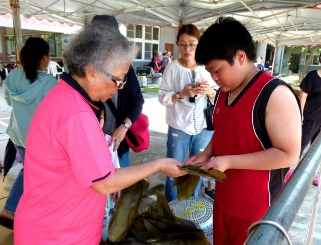 社區媽媽教小朋友包粽子。
