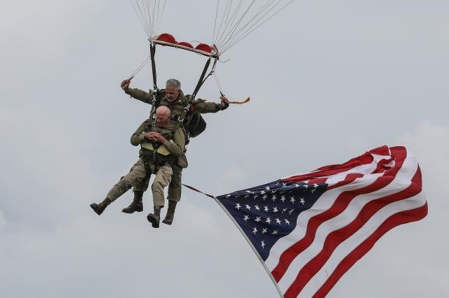 一面美國國旗在二戰老兵就是湯姆·賴斯(Tom Rice)身下飄揚。( LUDOVIC MARIN/Getty Images)