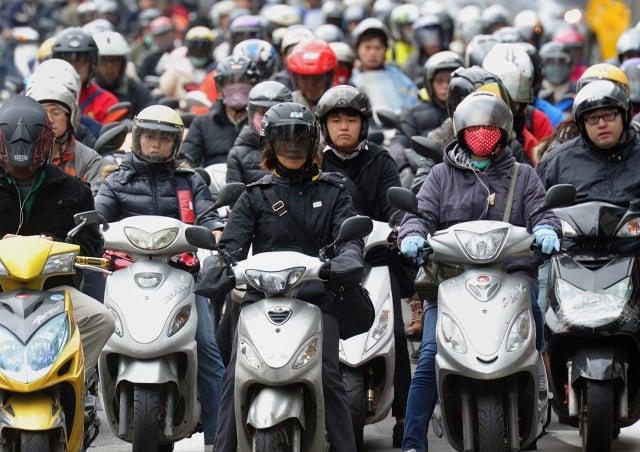 很多台灣人以機車代步。圖為2013年11月22日,台北居民騎機車上班。(SAM YEH/AFP/Getty Images))