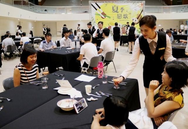 弘光科技大學在活動中心內擺了20多張桌子,鋪上黑色桌布、放上白色餐具,每一桌有一個學生服務,讓人彷彿走入高級西餐廳。
