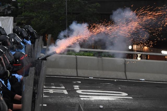 現場有記者採訪時被警察以近距離發射催淚彈、警棍痛擊等方式對待。香港記者協會發表聲明,嚴重譴責香港警方危害記者安全及損害新聞自由的行為。(Anthony WALLACE / AFP)