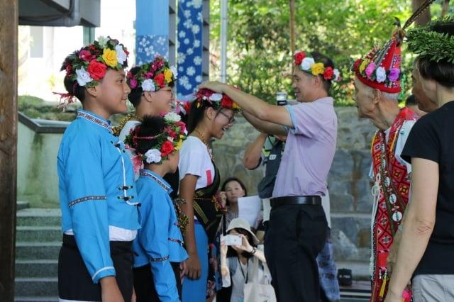 利嘉國小校長許忠文為學生戴上部落植物編織的花環。(台東林管處提供)