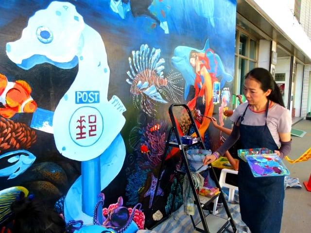 台東女中美術班教師康毓庭帶學生頂著高溫彩繪綠島豆丁海馬郵筒和海底世界。