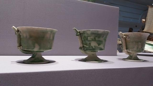 唐代鞏縣窯製作的白釉綠彩瓷吸杯。外面有一根吸管與杯底相連。(大紀元資料室)