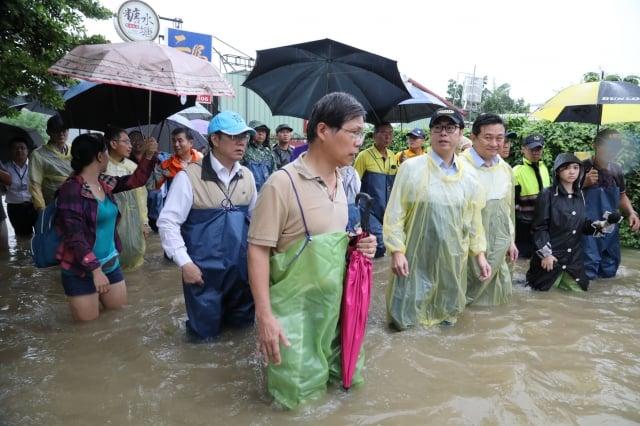 行政院副院長陳其邁(黃雨衣右2)抵達台南,在市長黃偉哲(左著青蛙裝)等陪同下,視察三爺宮溪等淹水地區。(台南市政府提供)