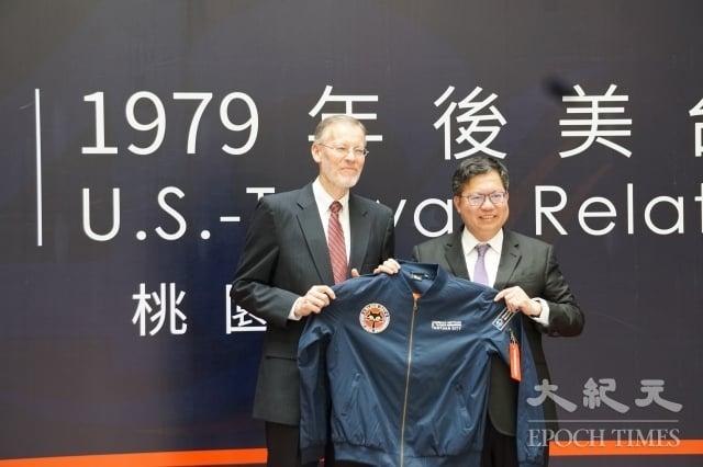 桃園市長鄭文燦(右)送印有黑貓中隊標誌外套給美國在台協會處長酈英傑。(記者 徐乃義/攝影)