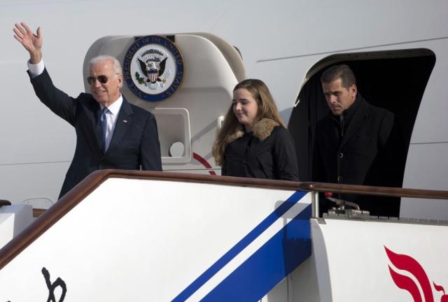 2013年12月4日,時任美國副總統拜登(左起)訪問中國大陸,他和他的孫女及兒子走出空軍二號時向人們揮手致意。(Getty Images)