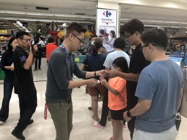 家樂福內湖店9月8日領先全台開賣山竹,工作人員發放號碼牌。