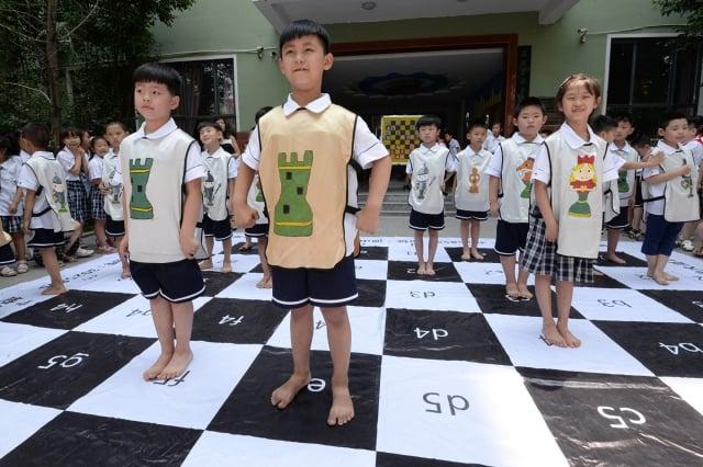 中共黑手伸向中國私立國際學校,學生被強制戴紅領巾。圖為2017年6月19日,河北省邯鄲市一所小學的孩子們在巨型國際象棋棋盤上下棋。(STR/AFP)