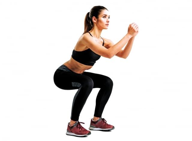 兩腳與肩同寬,雙手抱頭,像坐椅子般,將臀部往下拉,蹲到大腿與地板平行。可以的話,停一秒鐘左右,然後一邊吐氣,一邊伸直膝蓋與背肌,挺直腰桿。(shutterstock)