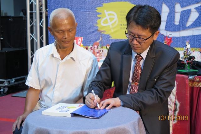 勞工局長吳威志(右)為黃連成師傅簽書。(記者黃玉燕/攝影)