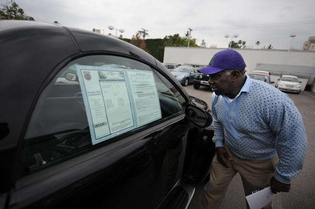 一個想買二手車的顧客正在閱讀《買家指南》。(ROBYN BECK/AFP via Getty Images)