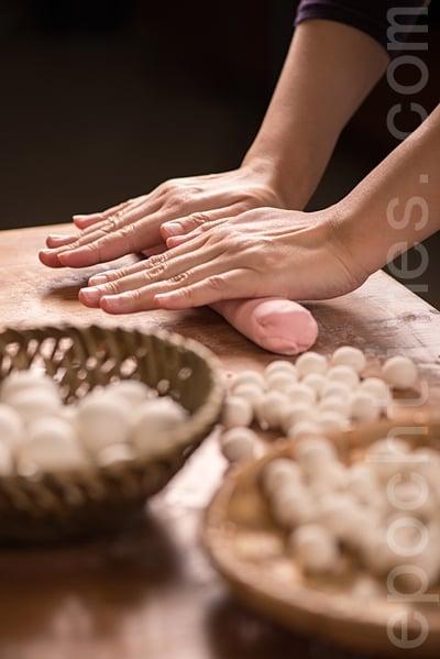 「搓湯圓」。先用軟滑的糰子為基底,把糯米粉屑黏合成糰,再分成小塊,搓成圓。(大紀元資料室)