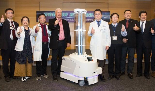 吳肇鑫副院長(右4)、感染科高智泉主任(左3)、友信醫療集團資深副總裁Mr.Ritzer(左4)等人與殺菌機器人合影。(童綜合醫院提供)