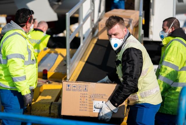 圖為義大利機場人員搬運從中國運來的醫療物資。( GEORG HOCHMUTH/APA/AFP via Getty Images)