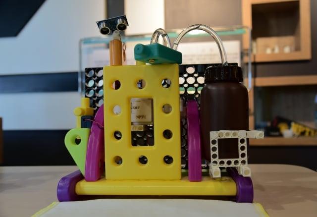 屏大學生以小學生常用的microbi電路板、智高積木,搭配紅外線感應器和外部馬達,設計出結構耐用、小學生也能動手做的自動酒精噴霧器。(屏東大學提供)