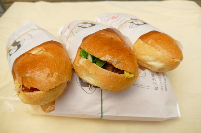 客人來法國麵包店裡,隨時買到剛出爐的熱麵包。(攝影/賴瑞)
