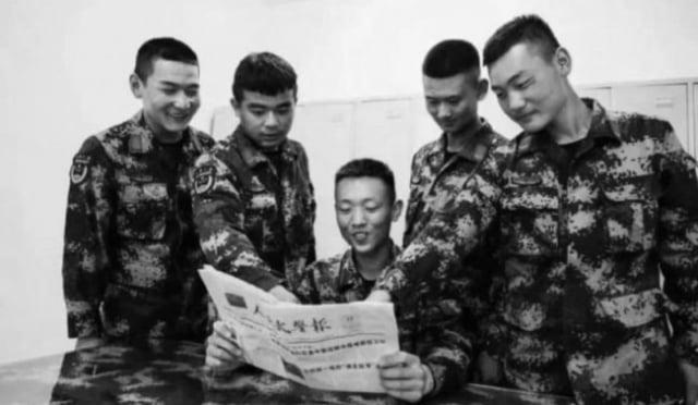 中共官媒宣傳照中,武警被發現其實是倒著看報。(微博擷圖)