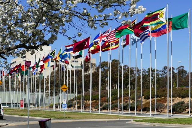法輪功理性和平反迫害21周年到來之際,來自30國逾600名政要共同簽署了一份聯合聲明,旨在聲援法輪功團體並呼籲共同制止仍在中國大陸發生且持續了21年的迫害。圖為澳洲首都堪培拉格里芬湖(Lake Burley Griffin)南岸的萬國旗。(安平雅)