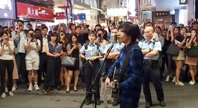 2019年10月24日晚,街頭藝人在中環唱英文版《願榮光歸香港》,被數名警察包圍恐嚇。藝人繼續以歌聲回應,聚集的市民越來越多,並一同合唱。(「看中國」影片擷圖)