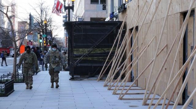美國總統拜登就職,華府高度戒備,到處是軍警,20日商家也釘上木頭確保安全。 (中央社)