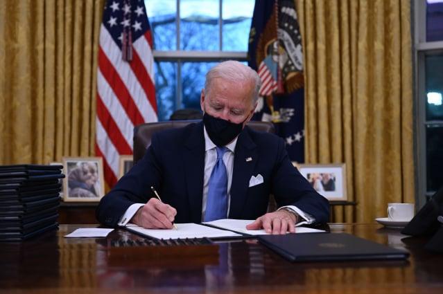 2021年1月20日,美國總統拜登在美國國會大廈宣誓就職後,坐在橢圓形辦公室裡簽署了一系列命令。包括決定重新加入《巴黎氣候協定》。( JIM WATSON/AFP via Getty Images)