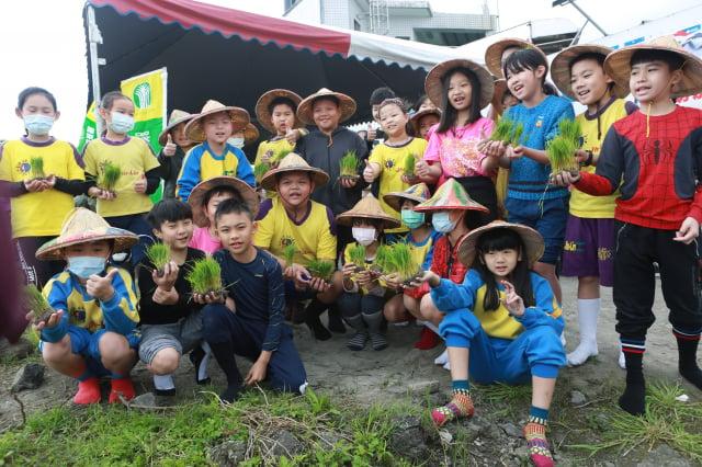 竹林國小學童們,脫掉球鞋、捲起褲管手拿秧苗,準備下田。