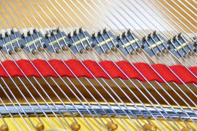 陳清流想到用扁平的銅片把通過琴橋的琴弦壓扁,讓聲音的能量釋放出更多,達到鋼琴演奏家需求的最佳效果。