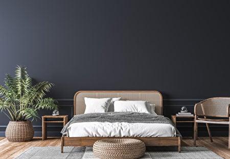 深色淨空的牆面凸顯籐製的大床和籐製傢俱。(Shutterstock)