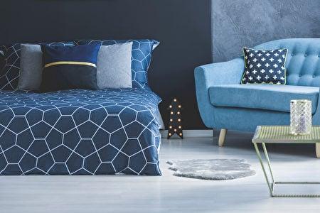 將不同漸層的藍色運用在牆面、沙發、抱枕、床罩上。(Shutterstock)