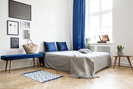深藍色窗簾、椅子坐墊、枕頭、床墊和小地毯。(Shutterstock)