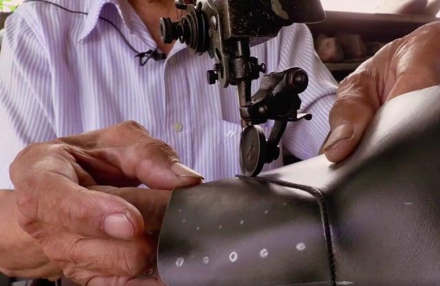 用手工仔細車縫皮鞋。(大紀元)
