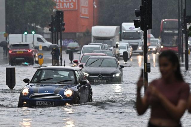 7月25日,倫敦受到暴雨襲擊,汽車駛過積水的路面。(JUSTIN TALLIS/AFP via Getty Images)