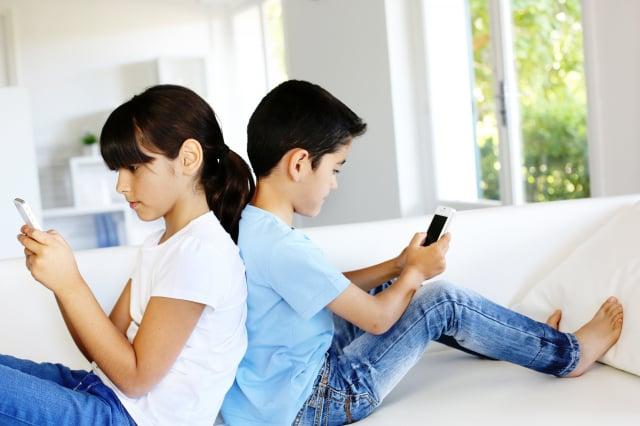 孩子們在使用手機。(Shutterstock)