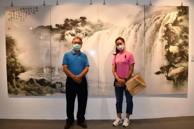 藝術家賴明郎(左)創作的水墨畫氣勢磅礡,成為展場的主視覺,吸引許多民眾搶著要和他合照。(記者賴月貴/攝影)