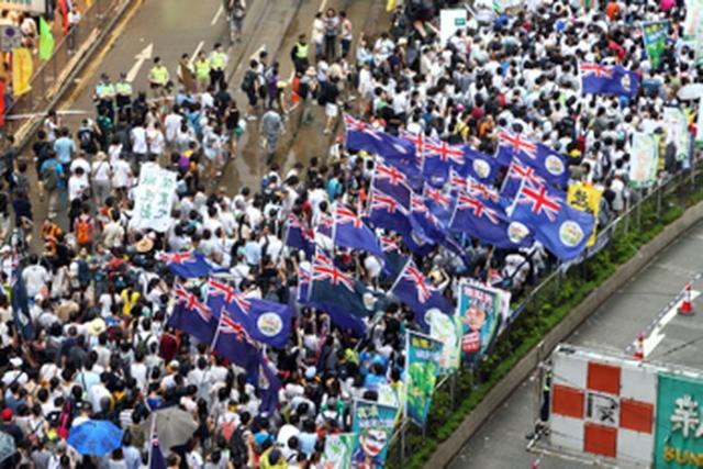 43萬港人無懼風雨參加七一遊行,高喊港共特首梁振英下台,圖為遊行人士高舉中共狠批的港英旗,手持港英旗的民眾說,是想表達對中共的不滿。(大紀元)