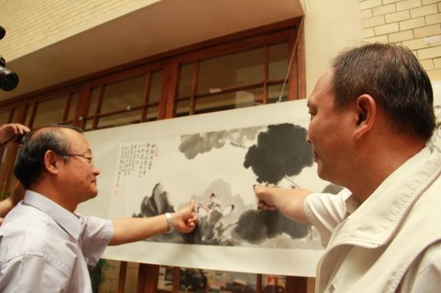 水墨畫大師林妙鏗(左)及縣長林聰賢(右)分別在畫作上留下手印印記。(記者謝月琴/攝影)