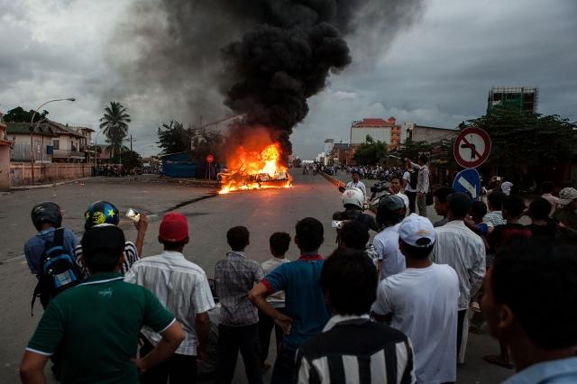 7月28日投票當天,選民抗議警方縱放舞弊人員,縱火燒警車。(Getty Images)
