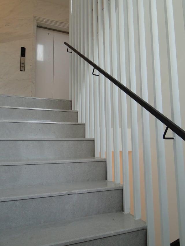 白色鋼琴烤漆的格柵貫穿全部樓層,黑色不鏽鋼扶手,搭配上大理石地面,營造梯間的冷調性。(記者謝平平/攝影)