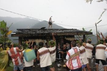 感恩祭主祭者登上祭屋屋頂,一聲令下,族人相互拋灑酒釀,並互祝身體健康及明年再慶豐收。(記者黃淑貞/攝影)