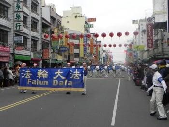 「台灣天國樂團」第3度應邀參加「嘉義市國際管樂節」的踩街活動,以開頭藍底金字的「法輪大法(Falun Dafa)」橫幅作為前導,途經嘉義城隍廟的盛況。(文/記者蔡上海、圖/記者蔡上海/攝影)