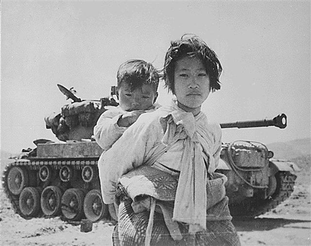 64年前的1950年6月25日南北韓間爆發的一場戰爭,至今仍處於停戰狀態。歷時3年的戰爭,對於中共、南韓、北韓,以及美國等參戰國誰是贏家,已無從說起,留下的只是對這場戰爭的真相、起因和非正義性的揭露和批判。圖為1951年6月5日的幸州山城,年幼的姐弟二人站在美式M-26坦克前。(AFP)