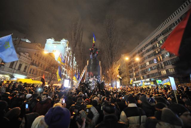 2013年12月8日,烏克蘭基輔,市中心的一座列寧塑像被推倒後,民眾站上原放置列寧像的底座歡呼慶祝。(AFP)