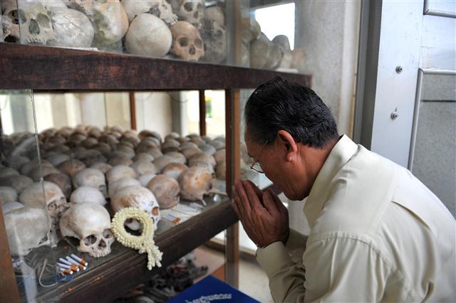 四十年前「紅色高棉」開始恐怖統治柬埔寨,短短幾年內殘殺四分之一國民。圖為昔日「殺戮戰場」之一改建的紀念館陳列遇難者骷髏頭。致意者為柬埔寨反對黨桑蘭西黨(現為柬埔寨救國黨)代理黨魁。(TANG CHHIN SOTHY / AFP )