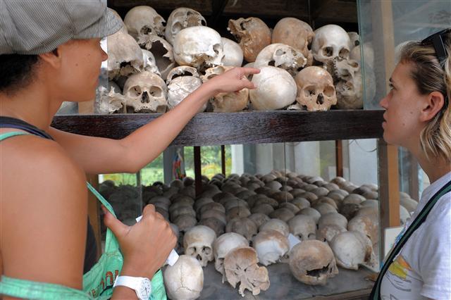 遊客參觀瓊邑克殺戮場紀念館陳列的罹難者骷髏頭。(TANG CHHIN SOTHY / AFP )