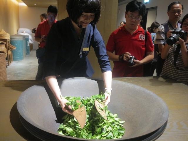 雙手輕輕攪拌茶菁的動作,可破壞葉緣細胞,使發酵順利進行。(攝影/鄧玫玲)