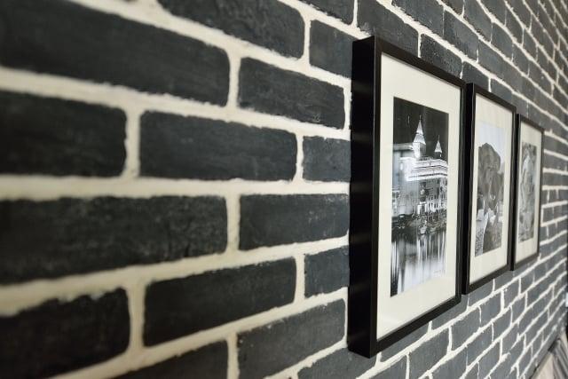 兩端的牆面跳脫文化石的色彩想像,運用黑白對比的文化石牆幾何形狀,展現意想不到的時尚觀點。(克俐凱文建築空間設計公司提供)